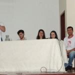 Acadêmico do 5º período, Igor Labre, de pé, tratando do Conselho da Pessoa Idosa; e bancada dos demais membros do GEDA que ministraram.